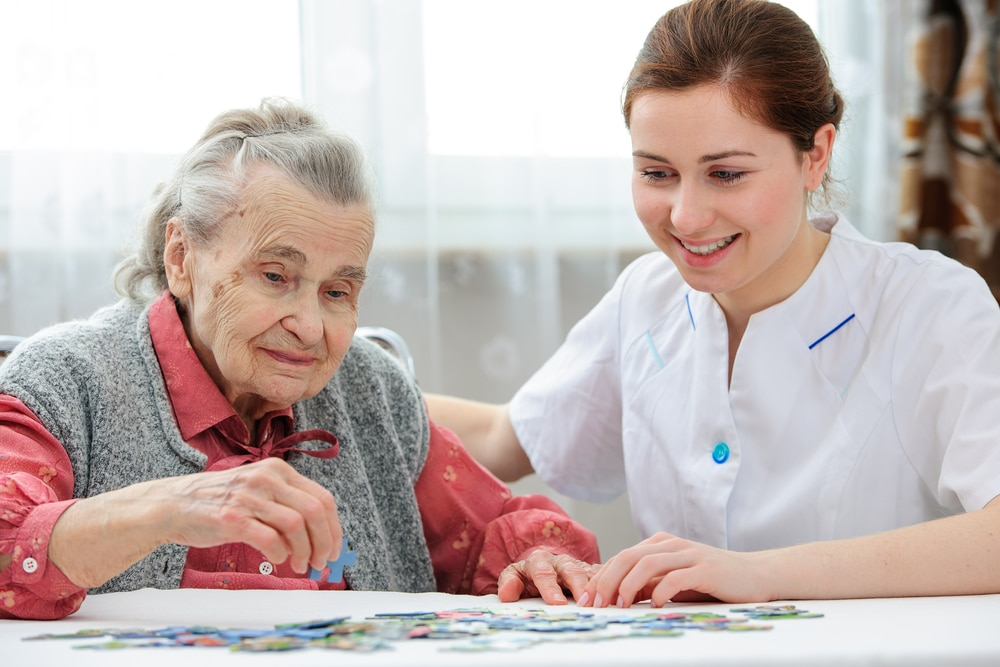 Elder care nurse playing jigsaw puzzle with senior woman in a memory care facility for Dementia Patients